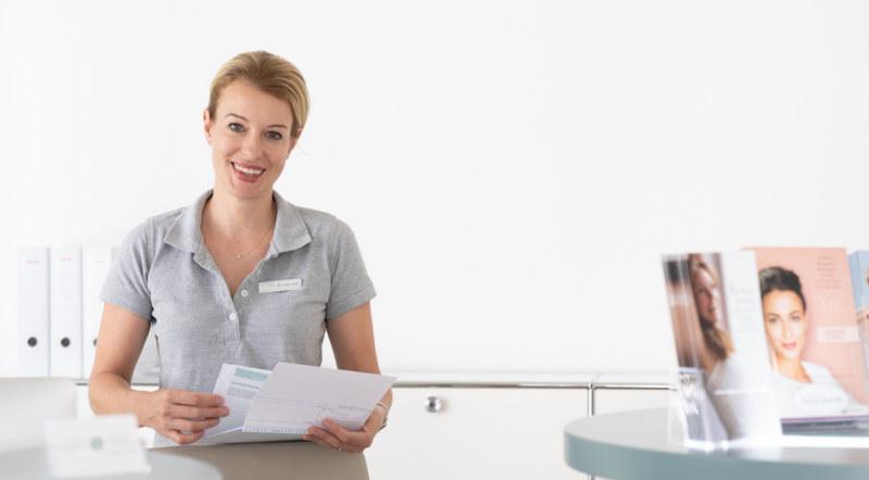 Weibliches Praxismitglied steht am Empfang der Praxis