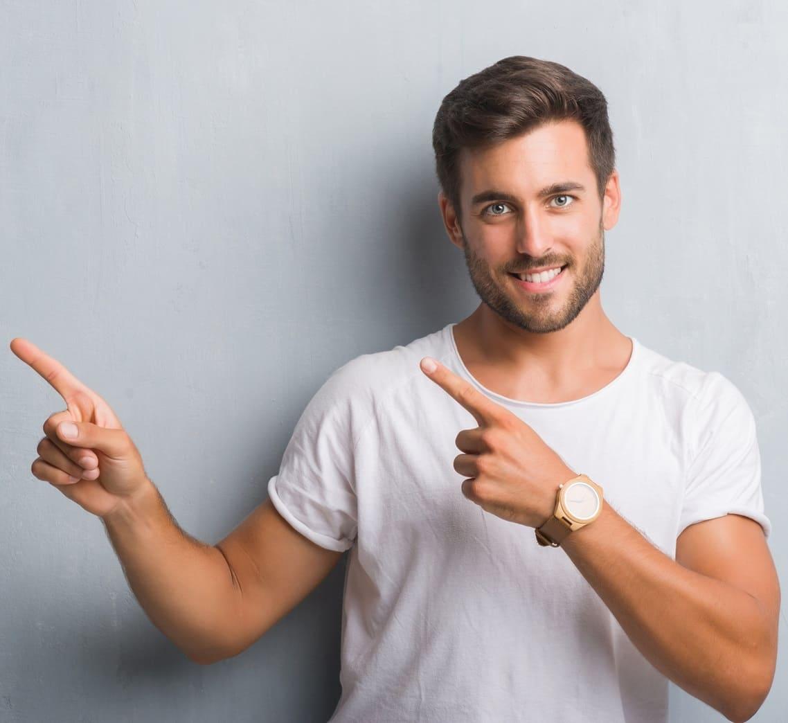 Ein Mann hebt die Zeigefinger in Richtung des linken Textblocks