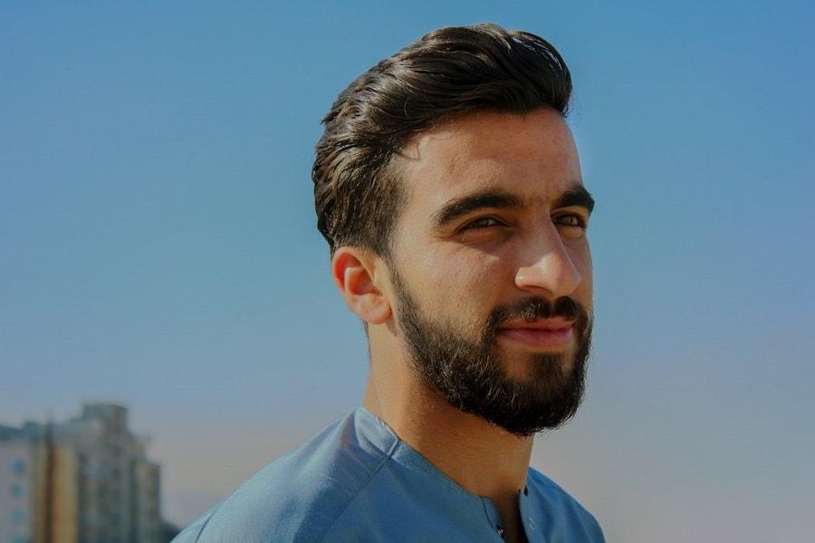 Ein junger Mann mit Bart und vollen Haaren vor blauem Himmel