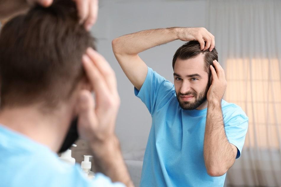 Mann betrachtet im Spiegel seine Geheimratsecken