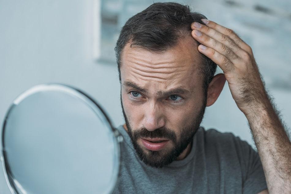 Mann prüft mit einem Handspiegel seine dünnen Haare