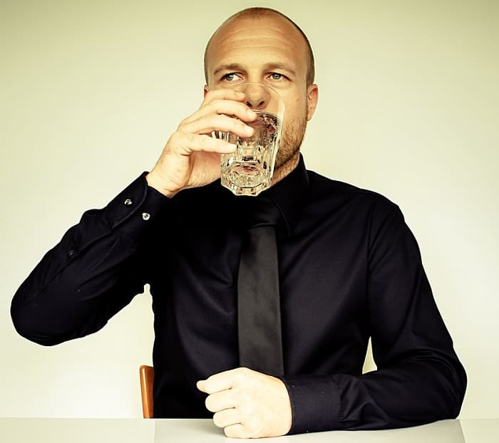 Mann trinkt Alkohol nach Haartransplantation