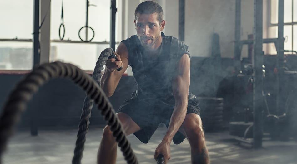 Mann im Fitnessstudio am Seiltrommeln