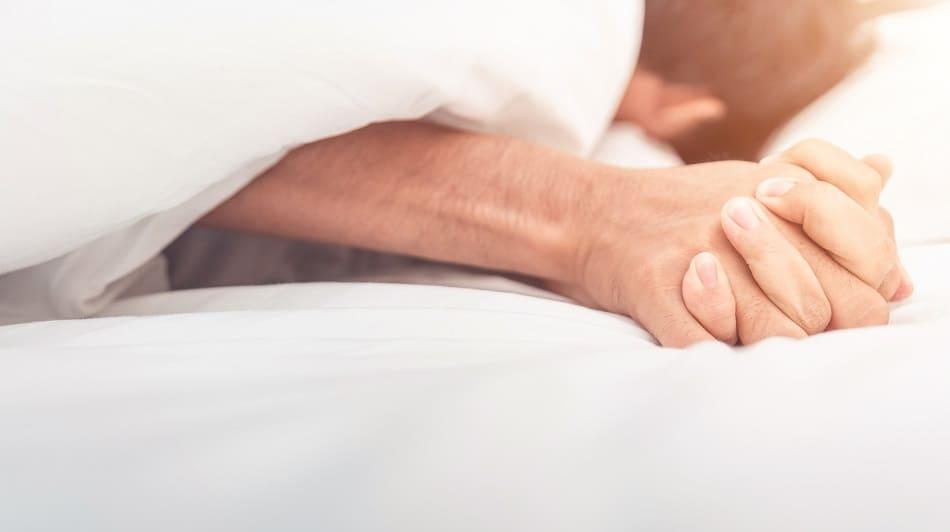Mann und Frau liegen im Bett und halten Händchen