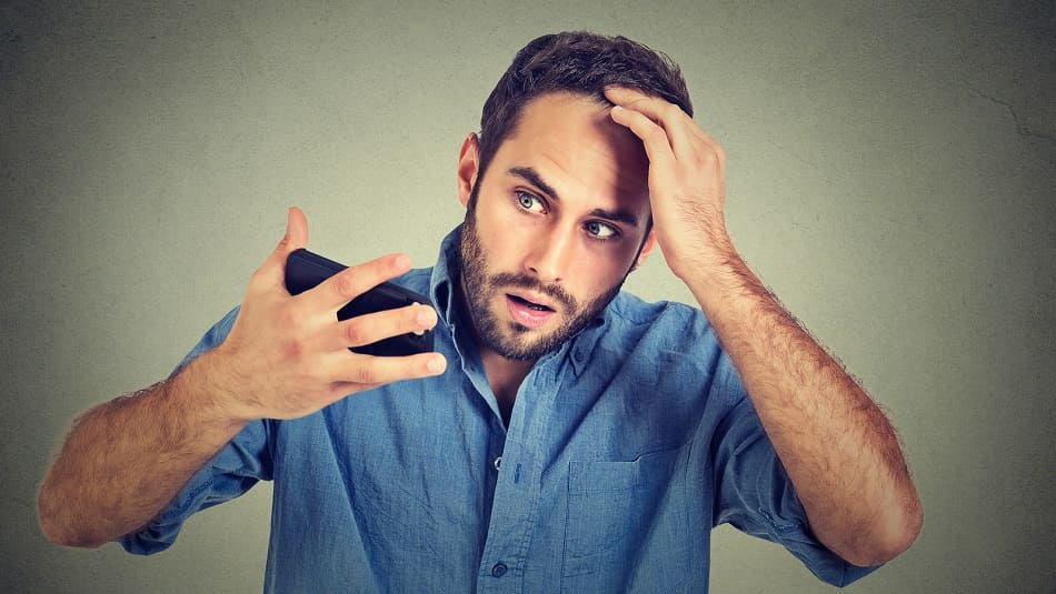 Ein Mann guckt sich schockiert seinen Haarausfall an