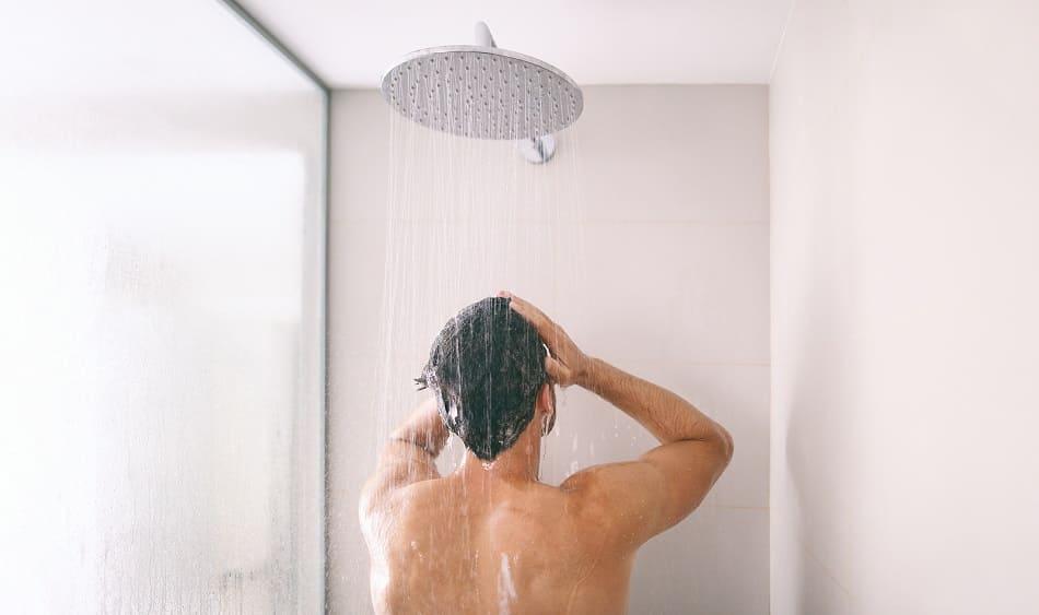 Mann unter Dusche waescht sich die Haare