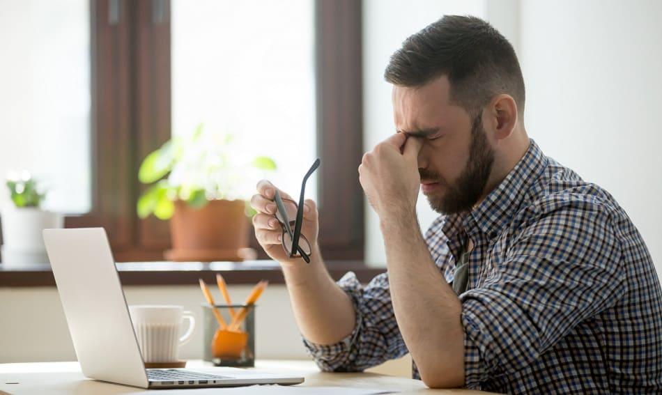 Mann sitzt gestresst vor seinem Laptop