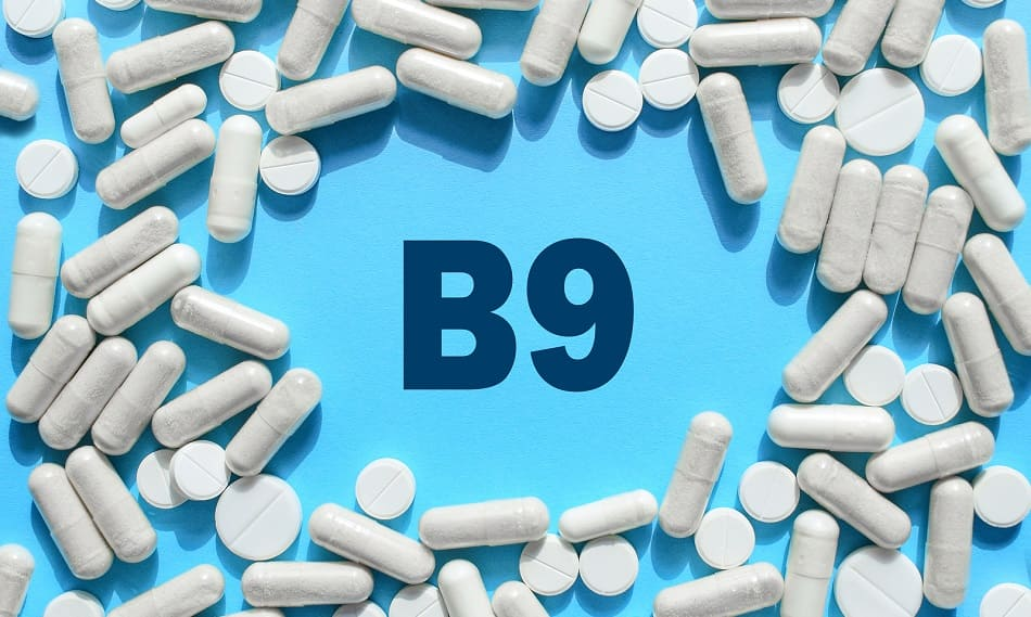 Vitamin B9 Text umgeben von diversen Tabletten und Kapseln