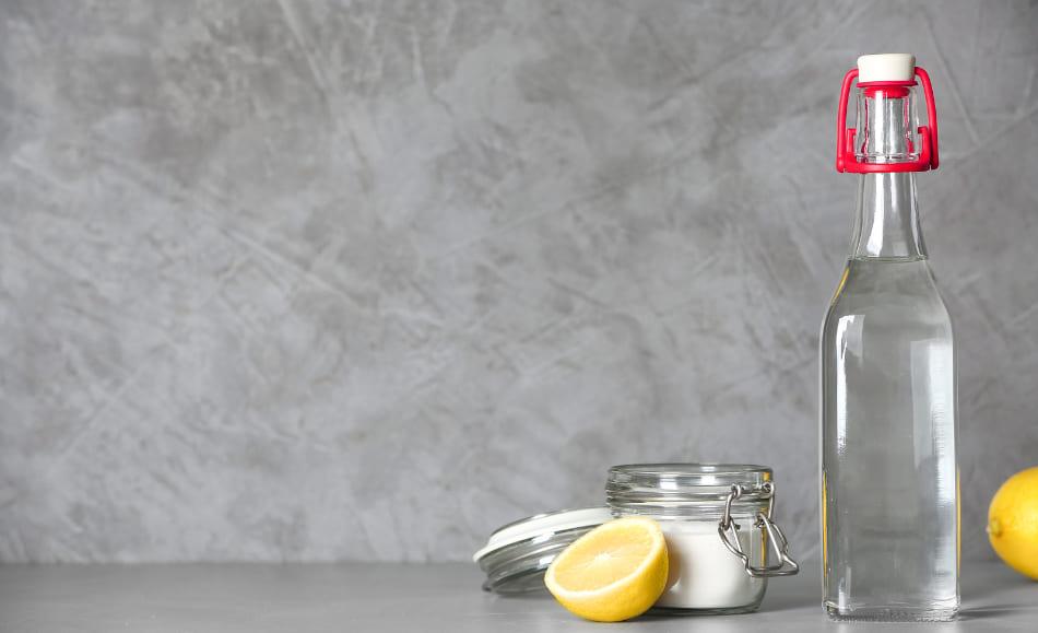 Eine Zitrone neben einer Flasche Essig