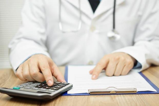 Arzt mit Taschenrechner sitzt am Tisch und berechnet die Kosten für die Barthaartransplantation