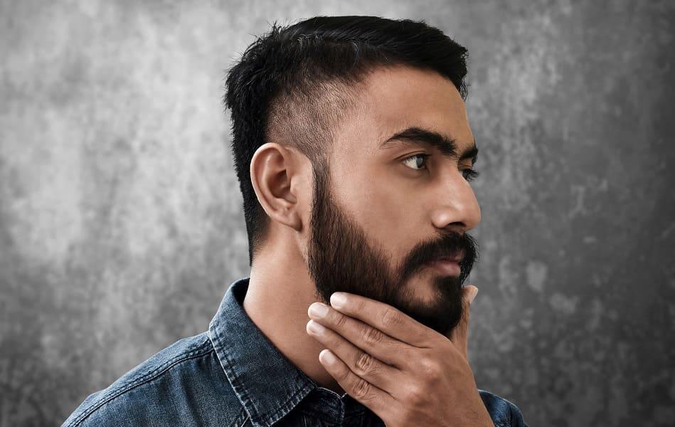 Seitenansicht von Mann, der sich mit der Hand durch den Bart streicht