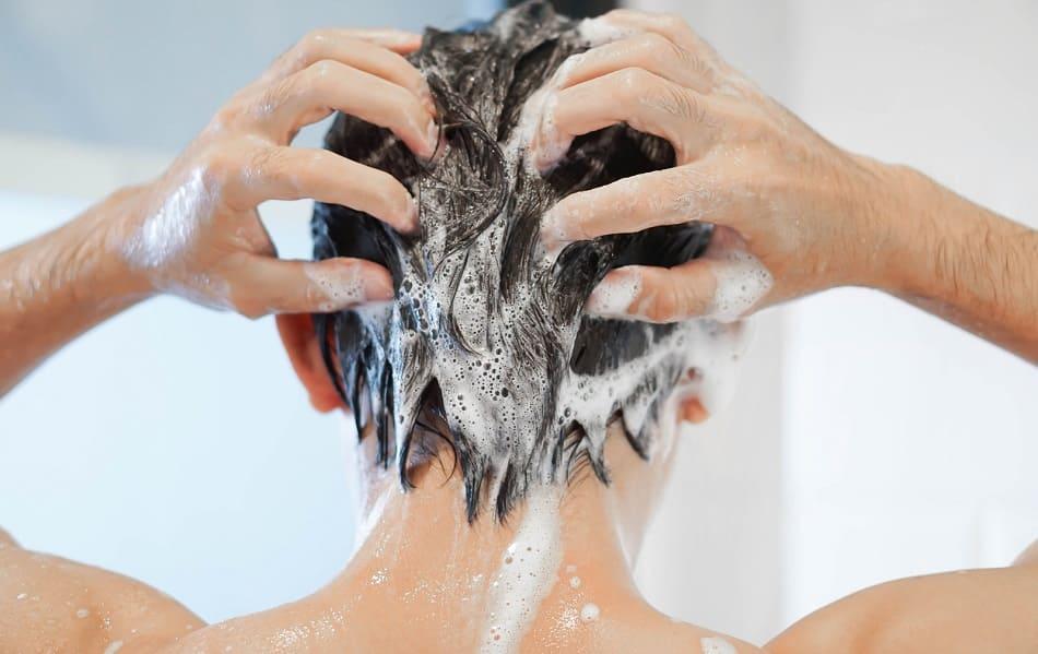 Rückenaufnahme von einem Mann der sich die Haare wäscht
