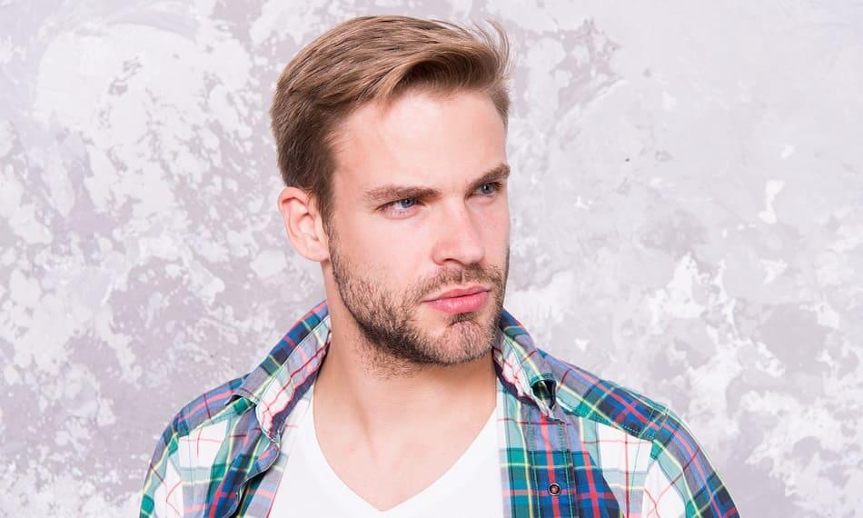 Junger Mann mit wenig Bartwuchs im Hemd vor einem grauen Hintergrund
