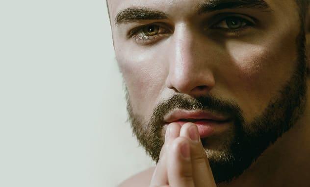 Mann mit leichtem Bartwuchs schaut frontal in die Kamera