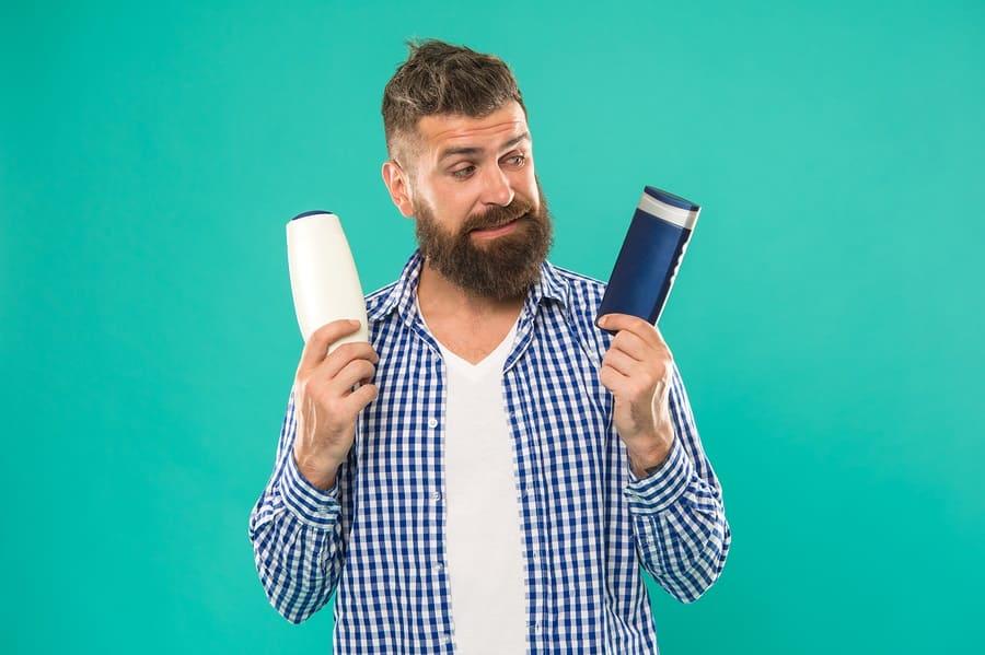 Mann mit zwei Flaschen Conditioner und Shampoo in beiden Händen vor einem grünen Hintergrund