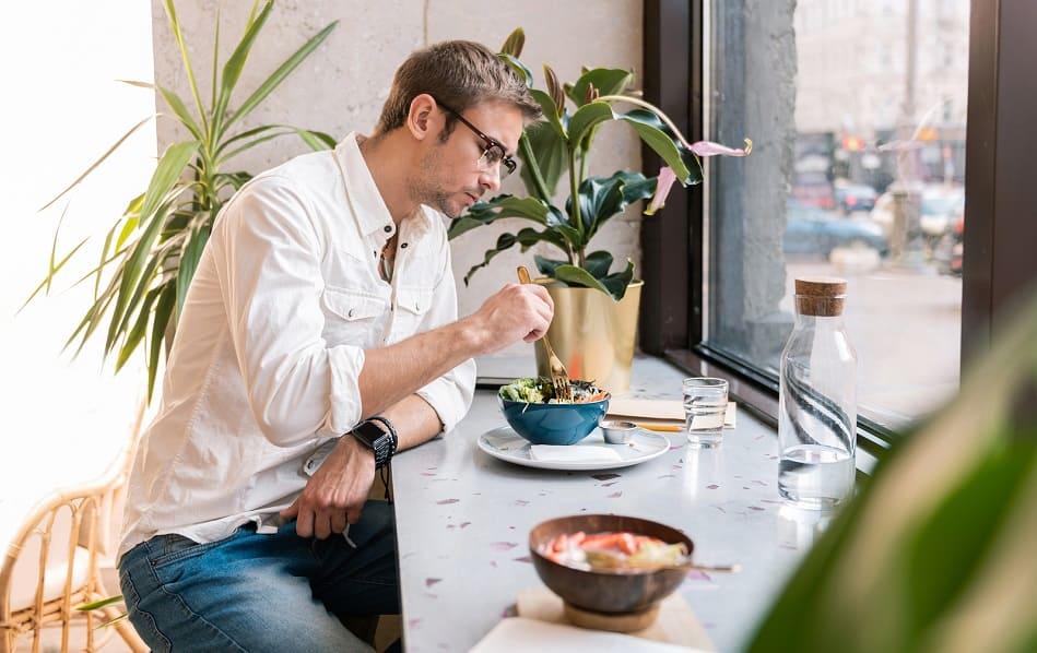 Mann sitzt in einem veganen Cafe und isst veganes Essen