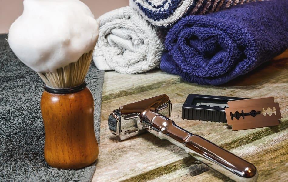 Nahaufnahme von Rasierpinsel mit Schaum, Rasierer, Rasierklinge und Handtüchern