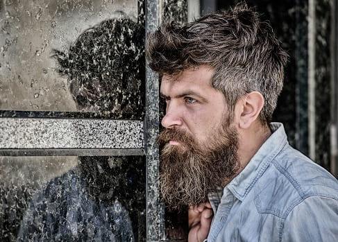 Mann mit Vollbart und Hemd posiert seitlich angelehnt an einer Wand