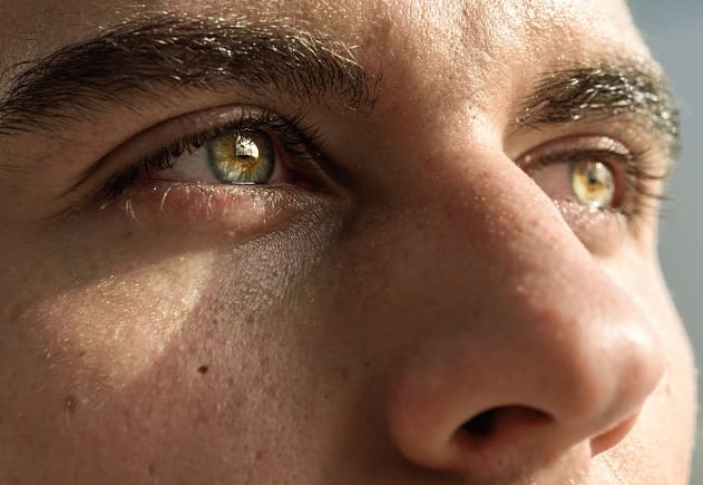 Nahaufnahme der Augen- und Nasenpartie eines Mannes mit grüngelben Augen