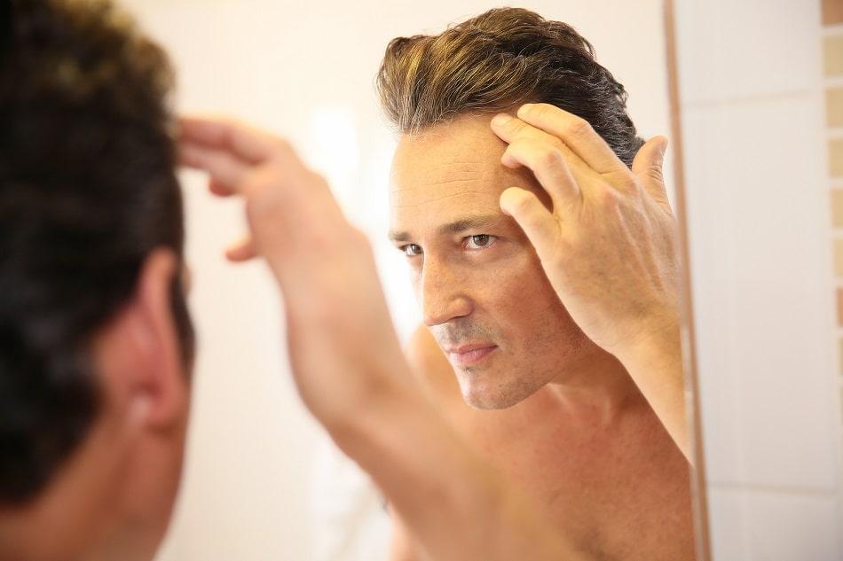 Mann mit Haarausfall vor dem Spiegel
