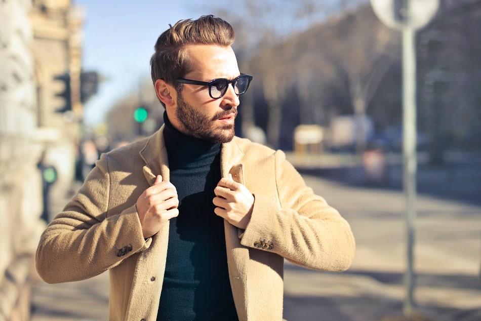 Mann ohne Bartluecken fässt sich an die Jacke und posiert auf der Straße