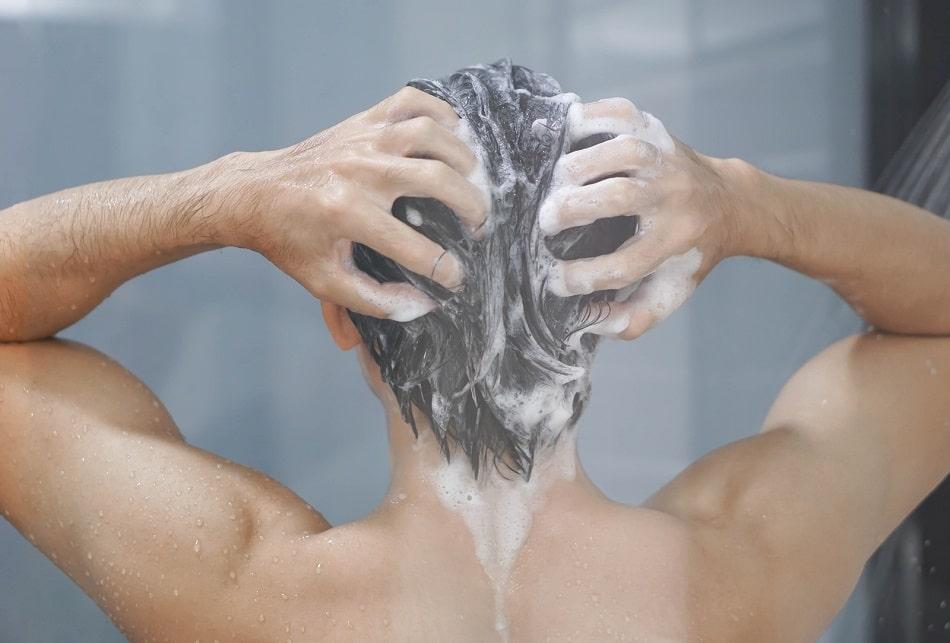 Mann shampooniert seine Haare