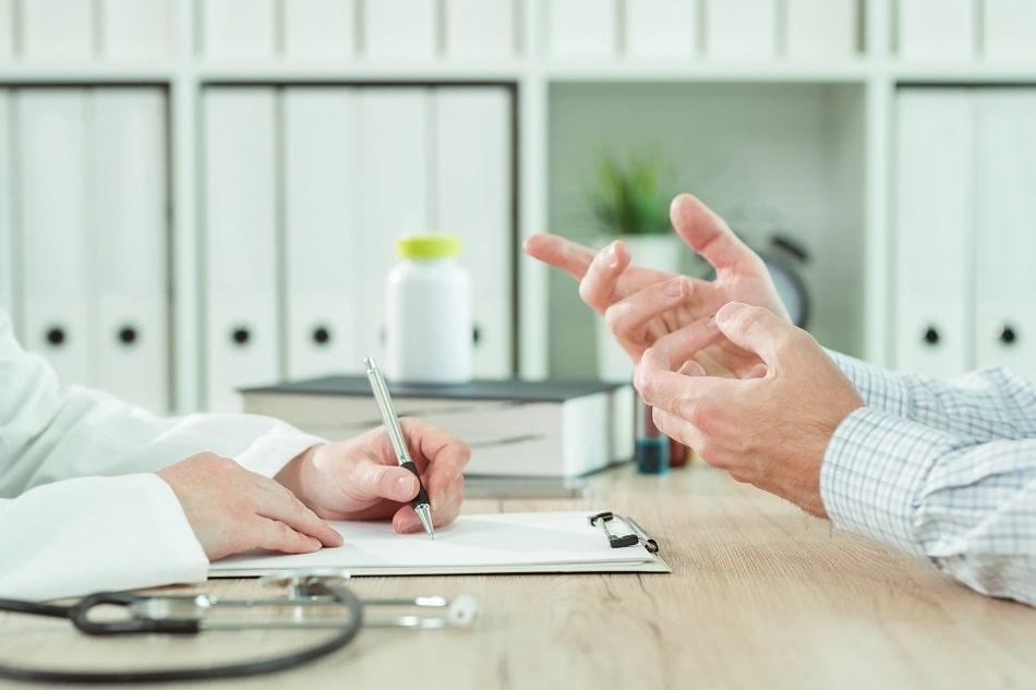 Arzt berät einen Patienten und macht sich dabei Notizen