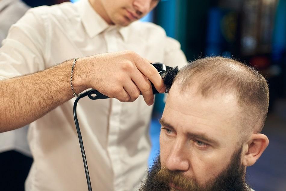 Mann mit Haarausfall beim Friseur