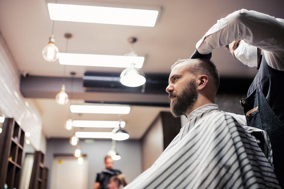 Friseur schneidet einem Kunden die Haare