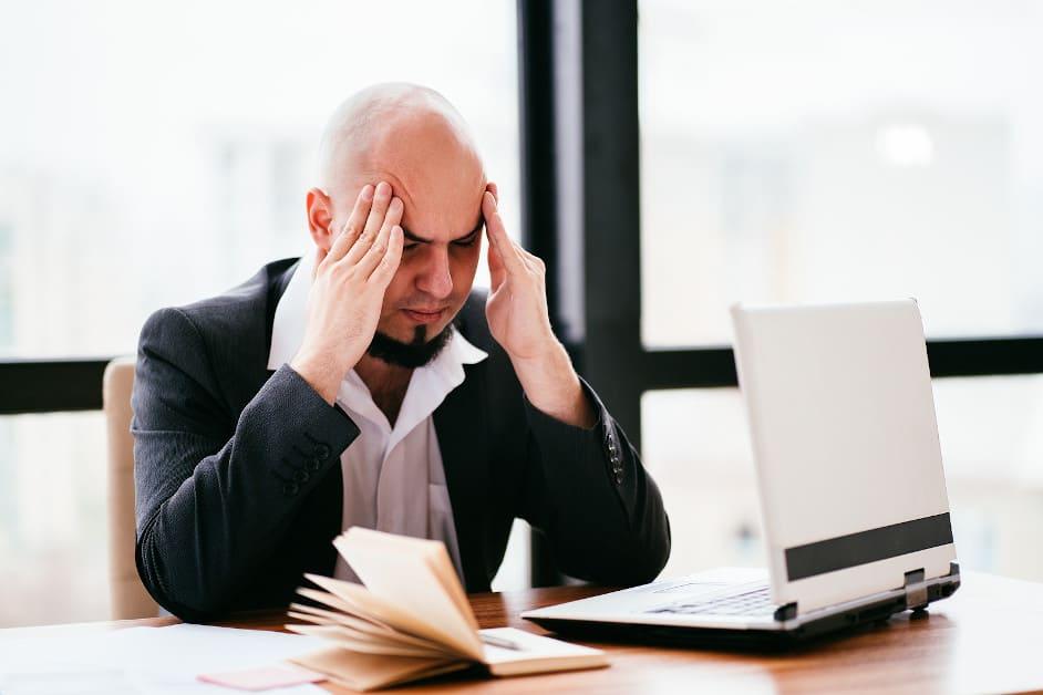 Gestresster Businessman sitzt vor seinem Laptop