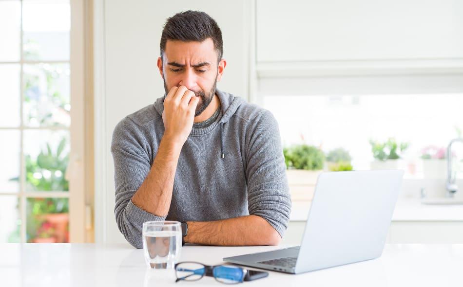 Junger Mann sitzt zuhause gestresst vor seinem Laptop