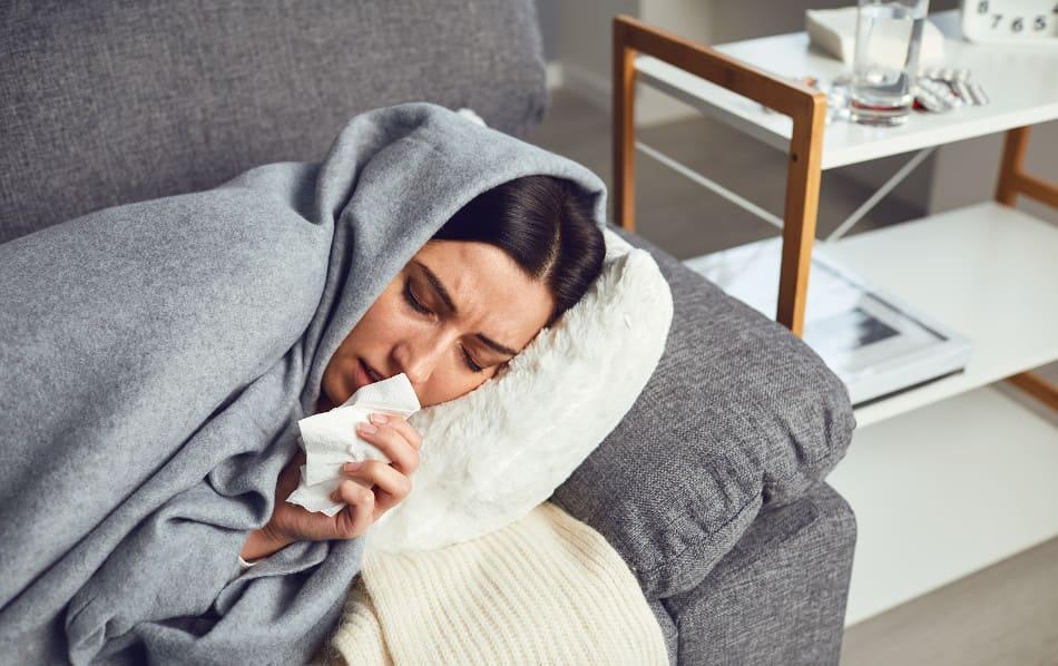 Frau liegt mit Coronavirus Symptomen auf der Couch
