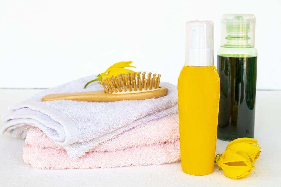 Verschiedene Haarpflegeprodukte neben einer Bürste und einem Handtuch