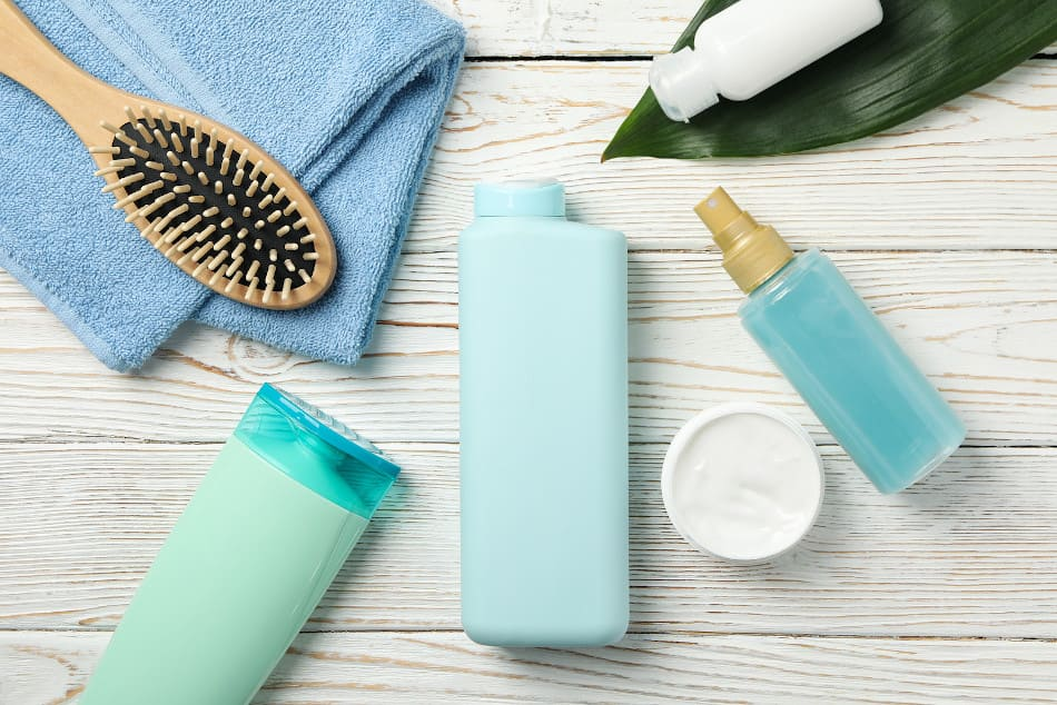 verschiedene Haarpflege Produkte liegen neben einer Bürste und einem Handtuch auf einem Holztisch