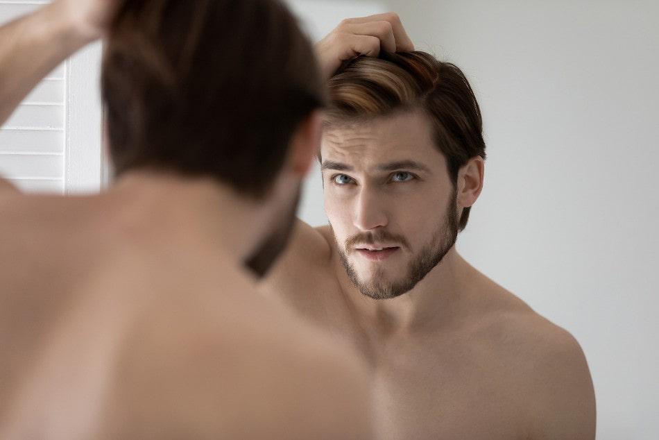 Mann mit einer Haar-Heterochromie inspiziert seine Haare vor dem Spiegel