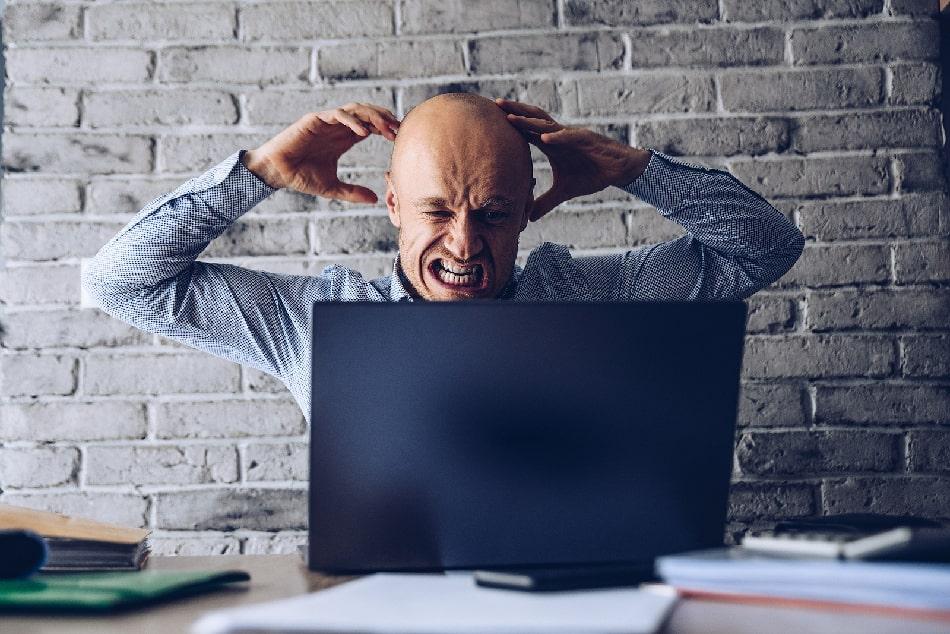Mann sitzt vor seinem Laptop, fässt sich an den Kopf und sieht gestresst aus