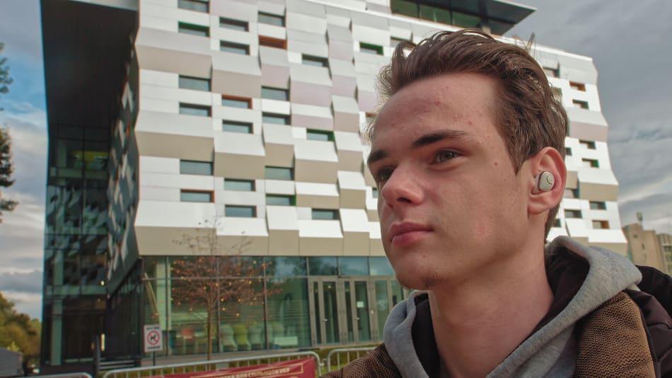 Teenager mit Haarausfall vor einem Hochhaus