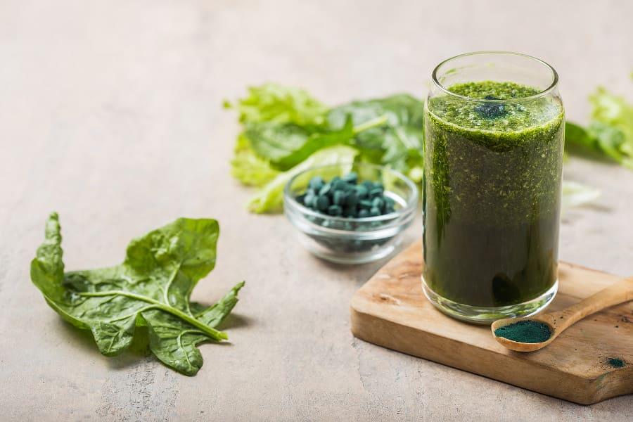 Smoothie aus Gerstengras gegen Haarausfall im Glas mit grünen Blättern.