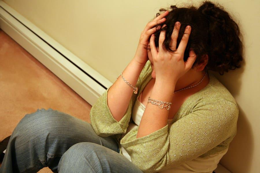 Mädchen sitzt auf dem Boden und leidet unter Haarausfall in der Pubertät