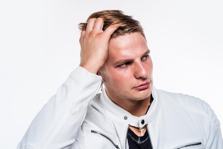 Junger Mann geht sich durch die vollen Haare nach einer Haartransplantation