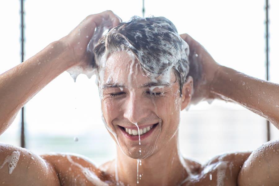 Mann wäscht seine Haare mit Shampoo als Haartransplantation Alternative