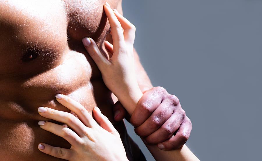 Mann hält die Hände einer Frau von seinem Sixpack fern, damit kein Sex nach der Haartransplantation passiert.