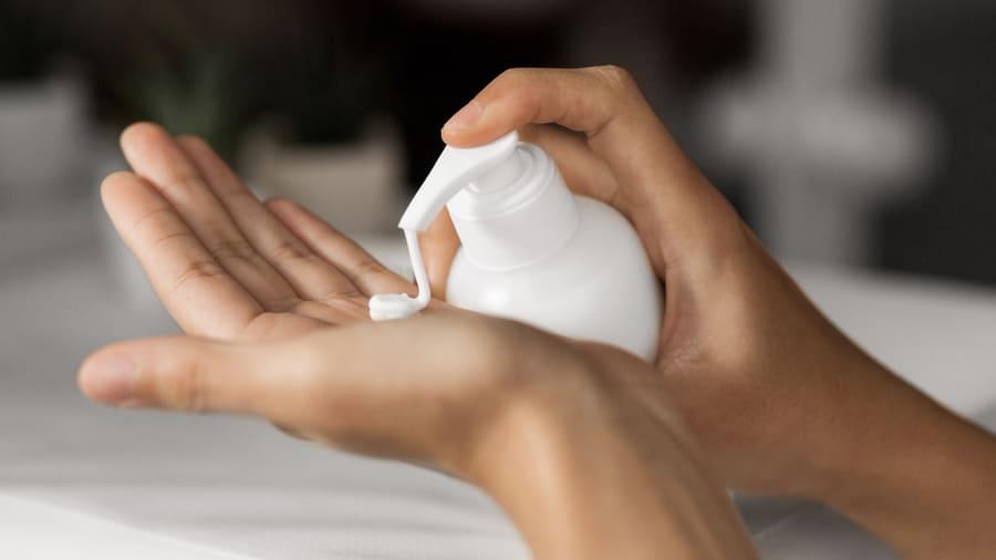 Bepanthen nach Haartransplantation wird aus Flasche auf Hand gedrückt zur Heilung durch Feuchtigkeit