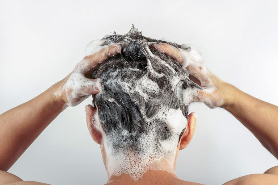 Mann wäscht seine Haare um das Haarwachstum nach der Haartransplantation zu fördern